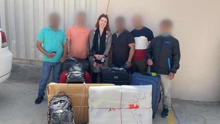 Victoria Fontan, accompagnée de gardes népalais, pose avec les bagages qu'elle devra laisser sur place, le week-end du 15 août 2021. (VICTORIA FONTAN)