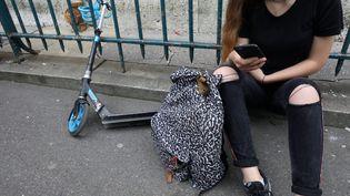Illustration d'une collégienne avec son téléphone portable. (YANN FOREIX / MAXPPP)