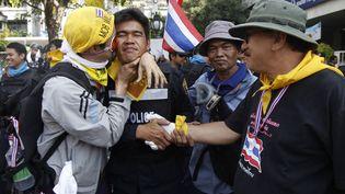 Des manifestants hostiles au gouvernement fraternisant avec un policier, à Bangkok (Thaïlande), le 3 décembre 2013. (CHAIWAT SUBPRASOM / REUTERS)