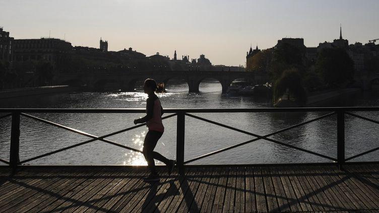 Une femme court sur le Pont des Arts, à Paris, le 8 avril 2020. (ALAIN JOCARD / AFP)