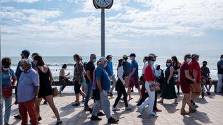 Des passants masqués profitent du soleil, samedi 29 mai 2021 à proximité de la plage de Saint-Gilles-Croix-de-Vie, en Vendée. (VALENTINO BELLONI / HANS LUCAS / AFP)