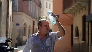 Un homme se rafraîchit à Perpignan, ville concernée par une alerte à la canicule, le 17 août 2012. (RAYMOND ROIG / AFP)