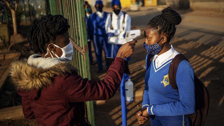 Prise de température àl'école secondaire Winnie Mandela de Tembisa, Ekurhuleni, le8 juin 2020. (MICHELE SPATARI / AFP)