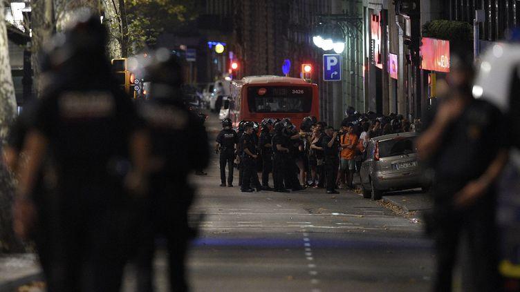 Des policiers espagnols regroupent des civils à Barcelone, jeudi 17 août, après qu'un véhicule a foncé sur La Rambla. (LLUIS GENE / AFP)