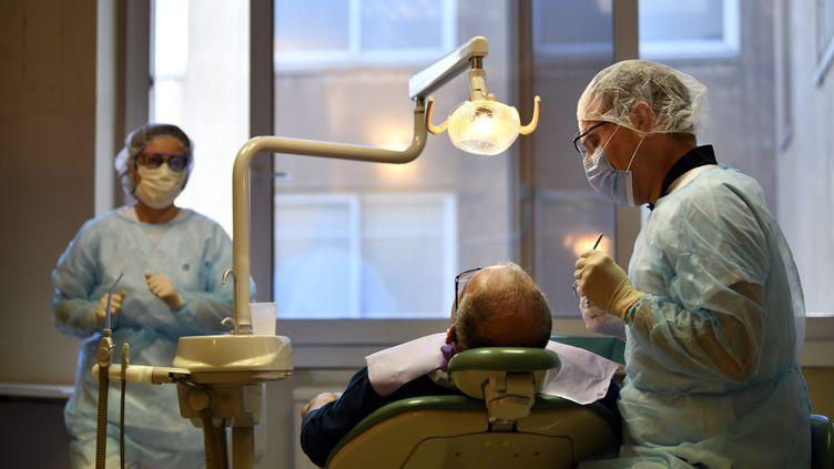 Un dentiste et son assistante traitent un patienturgentau service d'odontologie du CHRU de Nancy (Meurthe-et-Moselle), le 24 mars 2020, pendant le confinement qui a contraint les cabinets dentaires à fermer. (MAXPPP)