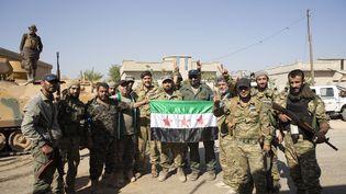 Des membres de l'Armée nationale syrienne posent avec un drapeau syrien en arrivant à Tell Abyad, en Syrie, dans le cadre de l'offensive menée par la Turquie, le 10 octobre 2019. (EMIN SANSAR / ANADOLU AGENCY / AFP)