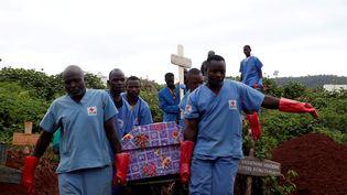 Des médecins de la Croix-Rouge enterrent une victime du virus Ebola, dans la ville de Butembo, en République démocratique du Congo, le 28 mars 2019. (BAZ RATNER / REUTERS)