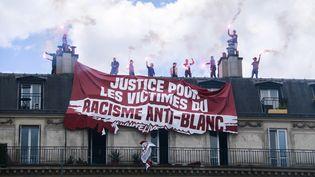 """Des activistes du mouvement Génération identitaire a déployé une banderoleappelant à la """"justice pour les victimes du racisme anti-blanc"""" lors de la manifestation contre les violences policières samedi 13 juin 2020 à Paris. (QUENTIN DE GROEVE / HANS LUCAS / AFP)"""