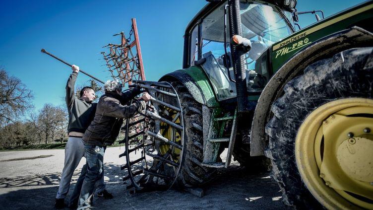 Des fermiers préparent un tracteur pour la culture des betteraves le 24 mars 2020 près de Troyes dans l'Aube. Le secteur agro-alimentaire est concerné par les ordonnances modifiant le droit du travail. (STEPHANE DE SAKUTIN / AFP)