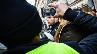 """Un manifestant filme un officier de police avec son smartphone pendant une manifestation des """"Gilets jaunes"""", le 14 décembre 2019 (AMAURY CORNU / HANS LUCAS)"""