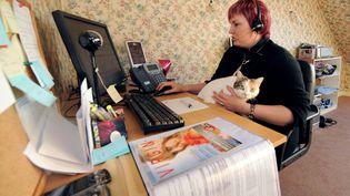 Une femme travaille chez elle pour un centre d'appels, à La Guerche-de-Bretagne (Ille-et-Vilaine). (MARCEL MOCHET / AFP)