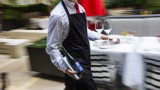Un serveur en plein travail. Photo d'illustration. (FRED DUFOUR / AFP)
