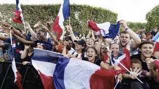 Des supporters fêtent la victoire de la France en Coupe du monde sur l'avenue des Champs-Elysées, à Paris, le 15 juillet 2018. (BERNARD MANIGAULT / CROWDSPARK / AFP)