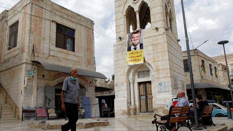 Une banderole s'en prenant à Emmanuel Macron déployée sur une place de Naplouse, en Cisjordanie occupée, le 25 octobre 2020. (MOHAMAD TOROKMAN / REUTERS)