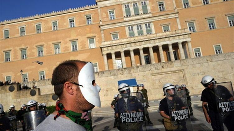 Un manifestant masqué près d'un cordon policier devant le Parlement grec à Athènes le 6 mai 2010. (AFP - DIMITAR DILKOFF)