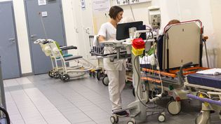 Une infirmière prodiguant les premiers soins à un patient installé dans le couloir des soins, dans le service des urgences du centre hospitalier de Martigues, dans les Bouches-du-Rhône, le lundi 23 septembre 2019. (GUILLEMETTE JEANNOT / FRANCEINFO)