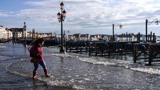 Une personne tente de traverser la ville de Venise, sous les eaux après une marée haute exceptionnelle, le 14 novembre 2019. (FILIPPO MONTEFORTE / AFP)