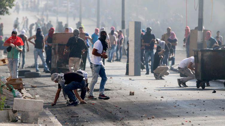 Des Palestiniens jettent des pavés contre des soldats israéliens, à Bethléem (Cisjordanie), le 16 octobre 2015. (MUHESEN AMREN / ANADOLU AGENCY / AFP)