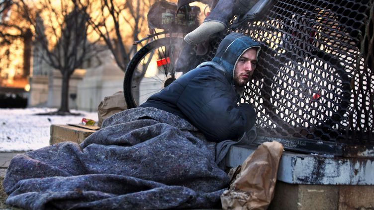 """Nicholas Simmons, 20 ans, tente de se réchauffer samedi 4 janvier 2014 dans une rue de Washington (Etats-Unis). Cette photo a été sélectionné pour faire la une de """"USA Today"""" le lendemain. (JACQUELYN MARTIN / AP / SIPA)"""