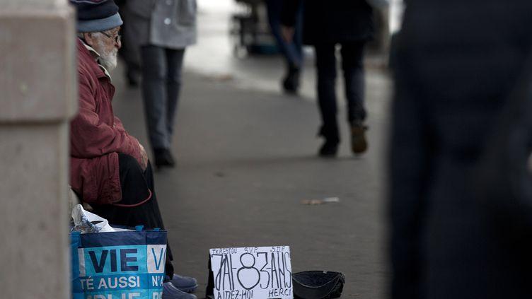 Un octogénaire fait la quête dans les rue de Paris, en novembre 2014. (JOEL SAGET / AFP)