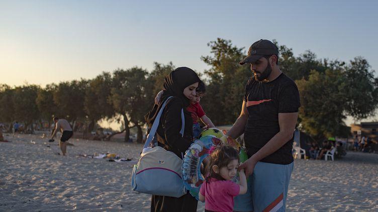 Une famille de réfugiés syriens sur la plage de Menekse, à Istanbul, le 28 juillet 2019. (YASIN AKGUL / AFP)