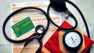 Une feuille de soins, une carte Vitale, un stétoscope et un tensiomètre dans un cabinet médical deGodewaersvelde (Nord),le 26 janvier 2012. (PHILIPPE HUGUEN / AFP)