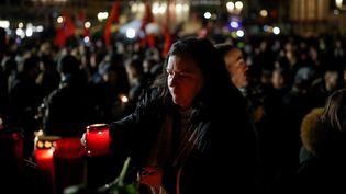 Une femme dépose une bougie lors de la soirée de recueillement à Hanau (Allemagne), le 20 février 2020. (ODD ANDERSEN / AFP)