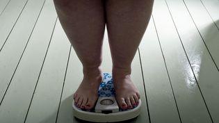 Une femme en surpoids se pèse sur une balance. (ROOS KOOLE/AFP)