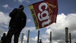 Un gréviste tientun drapeau de la CGT devant la raffinerie de Feyzin (Rhône), le 24 mai 2016. (JEFF PACHOUD / AFP)