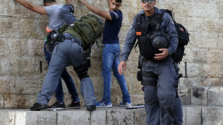 Des policiers israéliens fouillent de jeunes Palestiniens, à l'entrée de la vieille ville de Jérusalem, le 18 octobre 2015. (AHMAD GHARABLI / AFP)