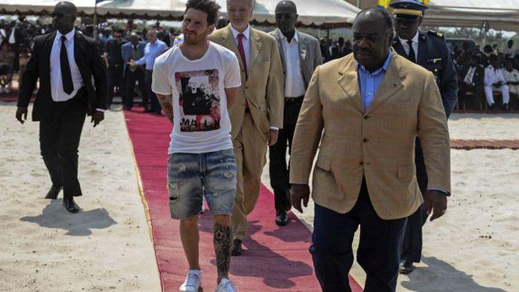 L'international argentin Lionel Messi (D), aux côtés du président gabonais Ali Bongo, le 18 juillet 2015 lors de sa visite à Port-Gentil (au Gabon) où il était invité à poser la première pierre du stade de la ville qui doit accueillir la CAN 2017. (AFP PHOTO / STEVE JORDAN)