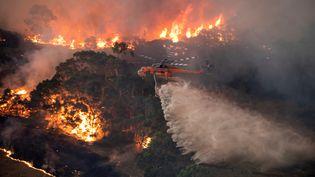 Un hélicoptère lutte contre le feu près deBairnsdale, en Australie, le 31 décembre 2019. (HANDOUT / STATE GOVERNMENT OF VICTORIA / AFP)