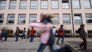 Des enfants jouent dans la cour d'une école primaire de Straubing, en Allemagne, le 11 décembre 2006. (ARMIN WEIGEL / DPA / AFP)