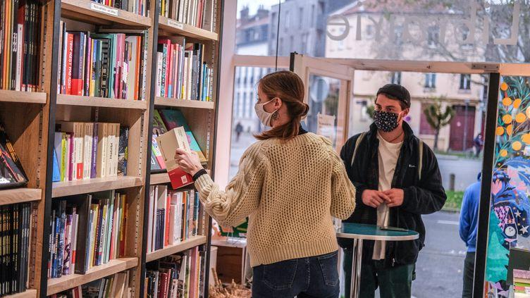 """Une libraire saisit un ouvrage vendu en """"click and collect"""" à un client durant le confinement à Lille (Nord) le 21 novembre 2020. (CELIA CONSOLINI / HANS LUCAS / AFP)"""