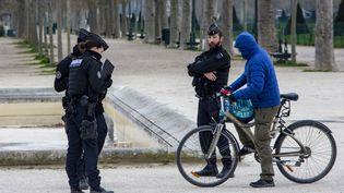 Une personne à vélo se fait contrôler sur le Champ-de-Mars, à Paris, le 21 mars 2020. (DOMINIQUE BOUTIN / SPUTNIK / AFP)
