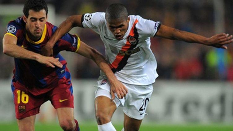 Douglas Costa (Shakhtar) à la lutte avec Busquets (Barça) lors du match aller (LLUIS GENE / AFP)