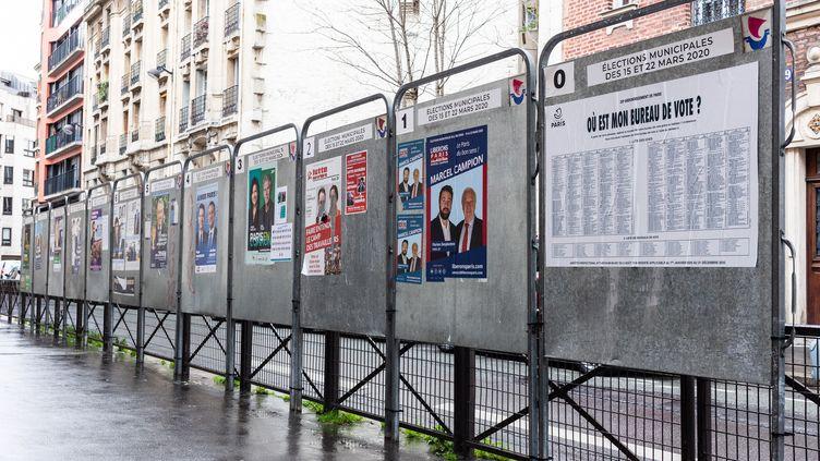 Des affiches présentant les candidats au premier tour des municipales à Paris, le 14 mars 2020. (AMAURY CORNU / HANS LUCAS / AFP)