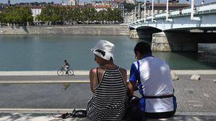 Un couple prend l'ombre sous un arbre, au bord du Rhône, dans la ville de Lyon, frappée par une vague de chaleur, le 7 août 2015. (PHILIPPE DESMAZES / AFP)