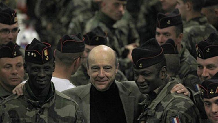 Le ministre de la Défense Alain Juppé au milieu des soldats français en Afghanistan, le 26 décembre 2010 (AFP/JOEL SAGET)