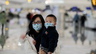 Une femme porte un enfant à l'aéroport de Pékin, la capitale chinoise, le 21 janvier 2020. (NICOLAS ASFOURI / AFP)