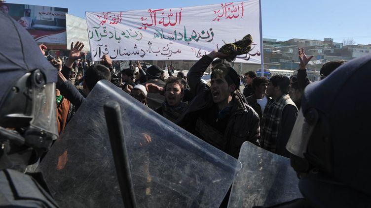 Des policiers anti-émeute afghansface à des manifestants qui protestent contre l'autodafé d'exemplaires du Coran, à Kaboul (Afghanistan), le 23 février 2012. (SHAH MARAI / AFP)