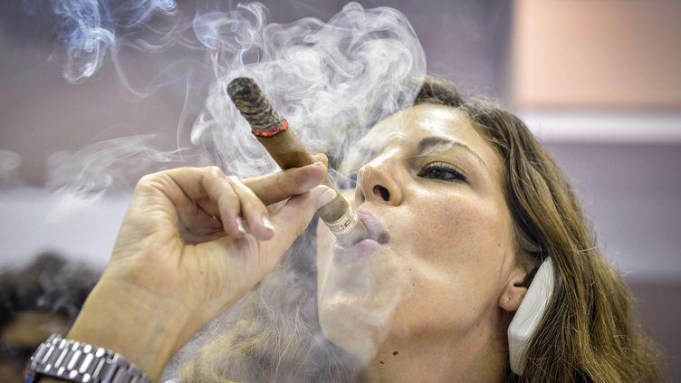 Une femme fume un cigare à La Havane (Cuba) lors duFestival du habano, le 27 février 2014. (ADALBERTO ROQUE / AFP)