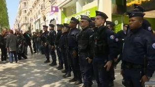 Des policiers qui patrouillent dans le quartier des Champs-Elyséesrendent hommage le 21 avril 2017 à leur collègue tué lors de l'attentat (FRANCE 2)