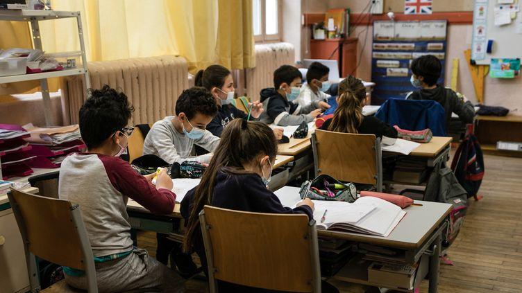 Des élèves d'élémentaire portent le masque en classe, le 26 avril 2021, dans une école de Bron, dans la métropole de Lyon. (SABINE GREPPO / HANS LUCAS / AFP)