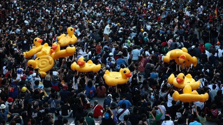 De gros canards gonflables sont passés dans la foule alors que des manifestants pro-démocratie se rassemblent pour un rassemblement anti-gouvernemental à un grand carrefour de Bangkok, le 18 novembre 2020. (JACK TAYLOR / AFP)