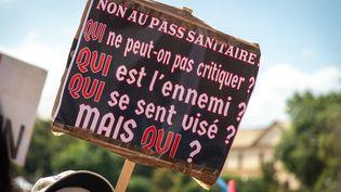 """Une pancarte brandie lors de la manifestation anti-pass sanitaire le 14 août à Metz, reprennant la réthorique du """"qui"""",devenue une référence discrète chez les militants antisémites. (NICOLAS BILLIAUX / HANS LUCAS VIA AFP)"""