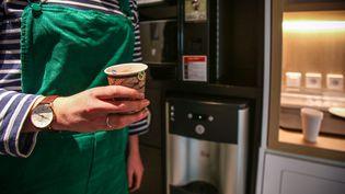 Une employée prend une pause pour boire un café, à Paris, le 2 avril 2019. (LILIAN CAZABET / HANS LUCAS / AFP)