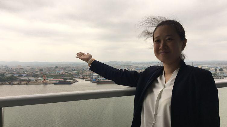 Madame Zhangmontre la Corée du Nord visible depuis un complexe immobilier qu'elle gère commercialement. (Radio France/Dominique André)