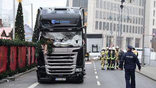 Un policier et des pompiers le 20 décembre 2016, près du camion qui a foncé sur la foule la veille, à Berlin (Allemagne). (TOBIAS SCHWARZ / AFP)
