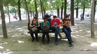 Alex, Abi, Yann et Hélène (de gauche à droite) jouent à Pokémon GO au jardin du Luxembourg, à Paris, le 14 juillet 2016. (LOUIS SAN / FRANCETV INFO)